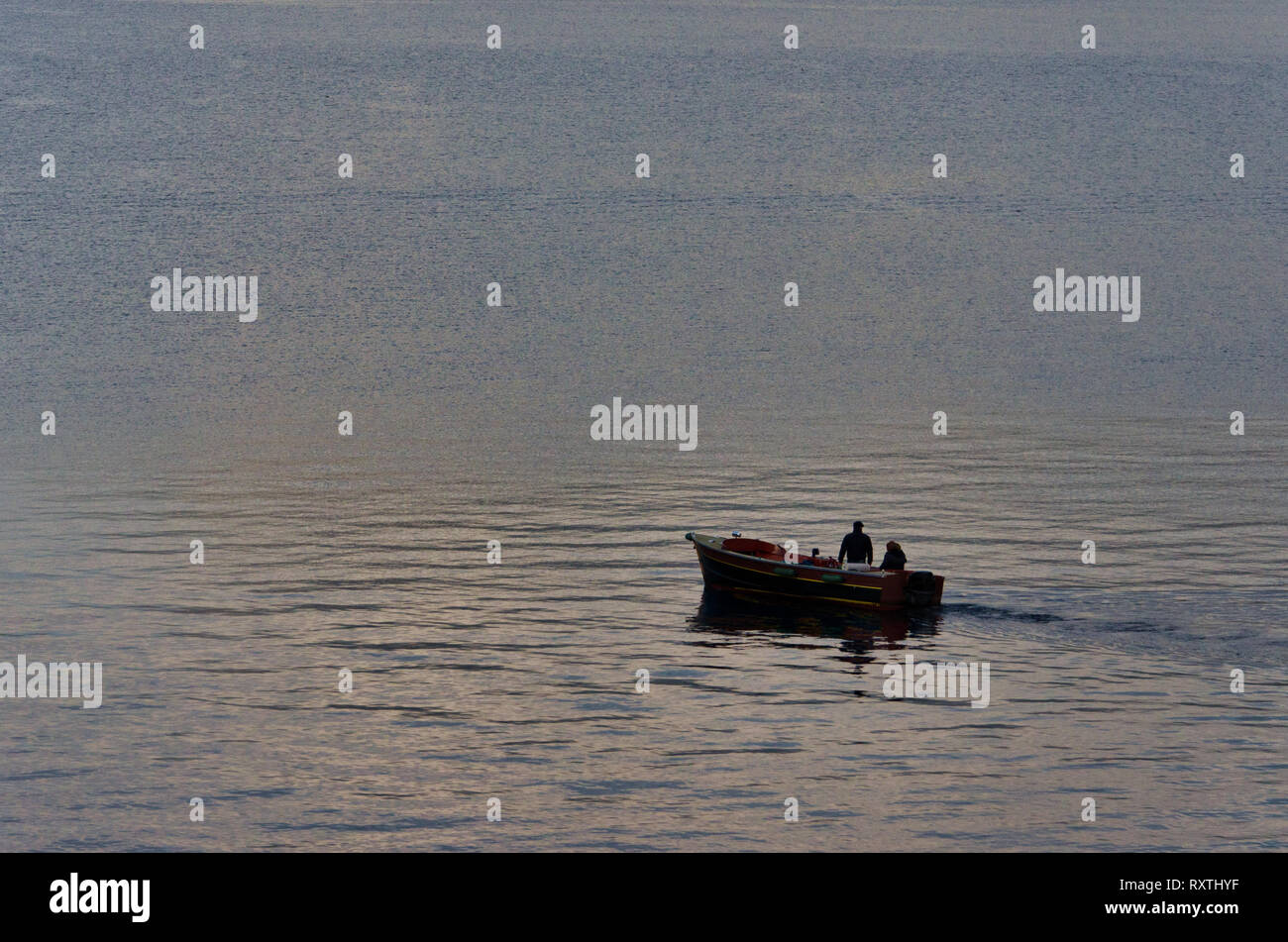 Little boat with two fishermen on the lake at down, light reflection on the water, rough water surface, tranquil scene from Lake Iseo in Italy - Stock Image