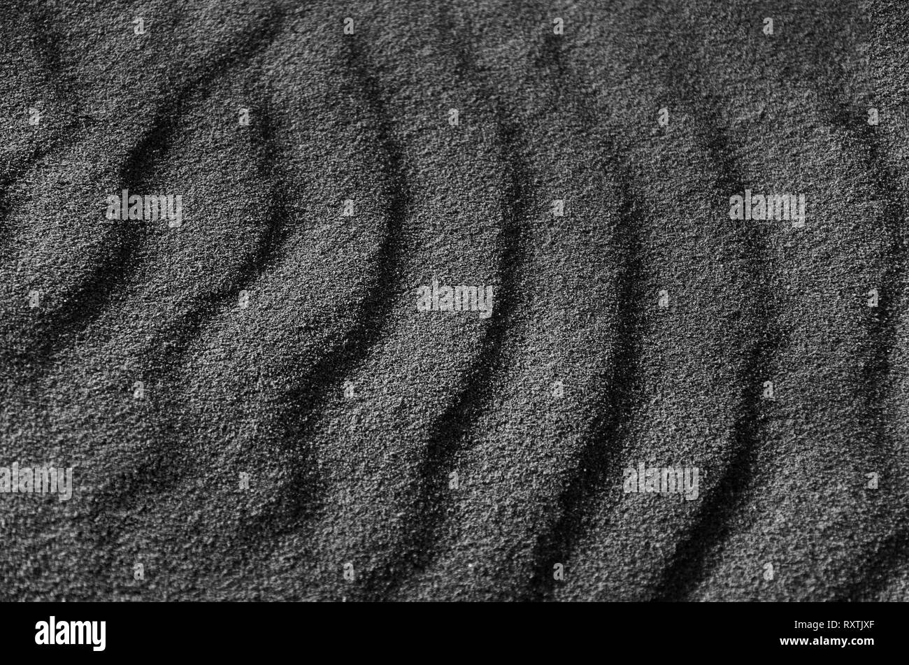 monochromatic photograph of the sand in the sea, abstract gray background, dark lines pattern, grainy texture - Stock Image