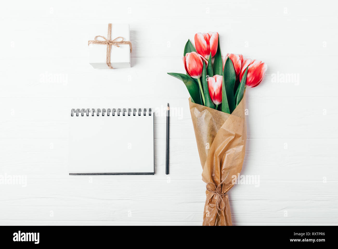 Flat Lay Arrangement Of Blank Notepad Template Near Small Gift Box And Bouquet Of Red Tulip Flowers In Brown Paper On White Wooden Desk Top View Stock Photo Alamy