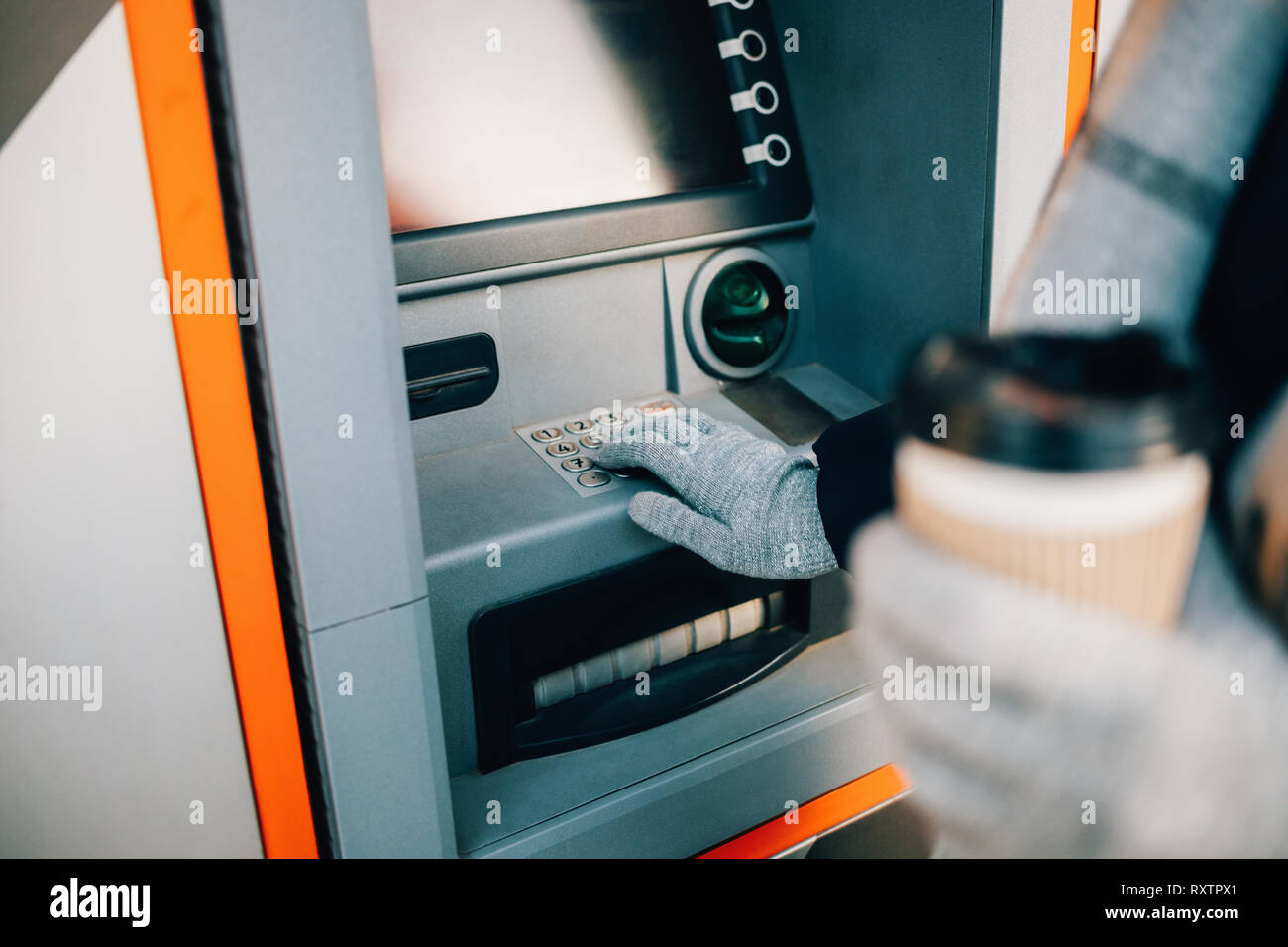 Unrecognizable young woman pressing buttons on ATM keypad entering PIN and drinking coffee on city street in winter day, close-up. - Stock Image