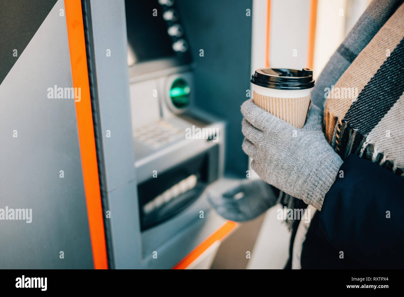 Close-up of unrecognizable young woman withdrawing cash using ATM on city street in winter day. - Stock Image