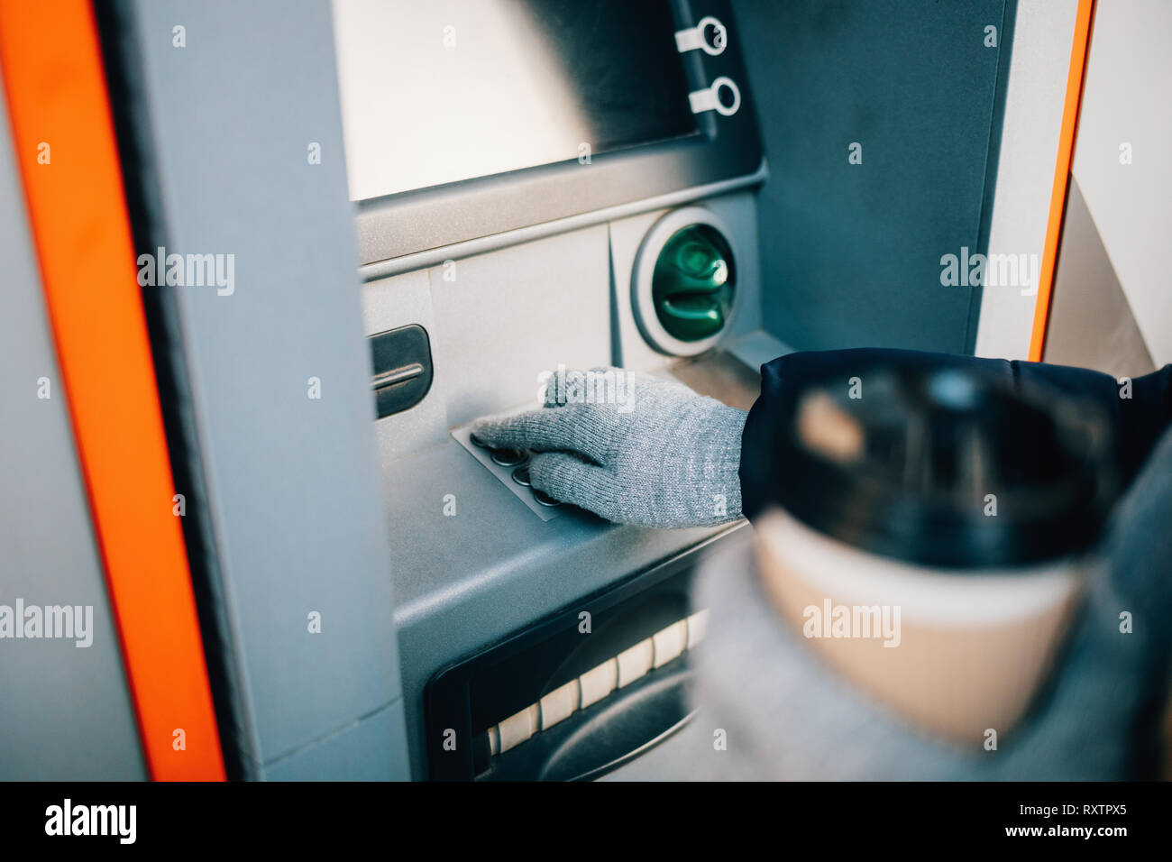 Close-up of young woman's hands holding coffee and entering PIN on ATM keypad on city street in winter day. - Stock Image