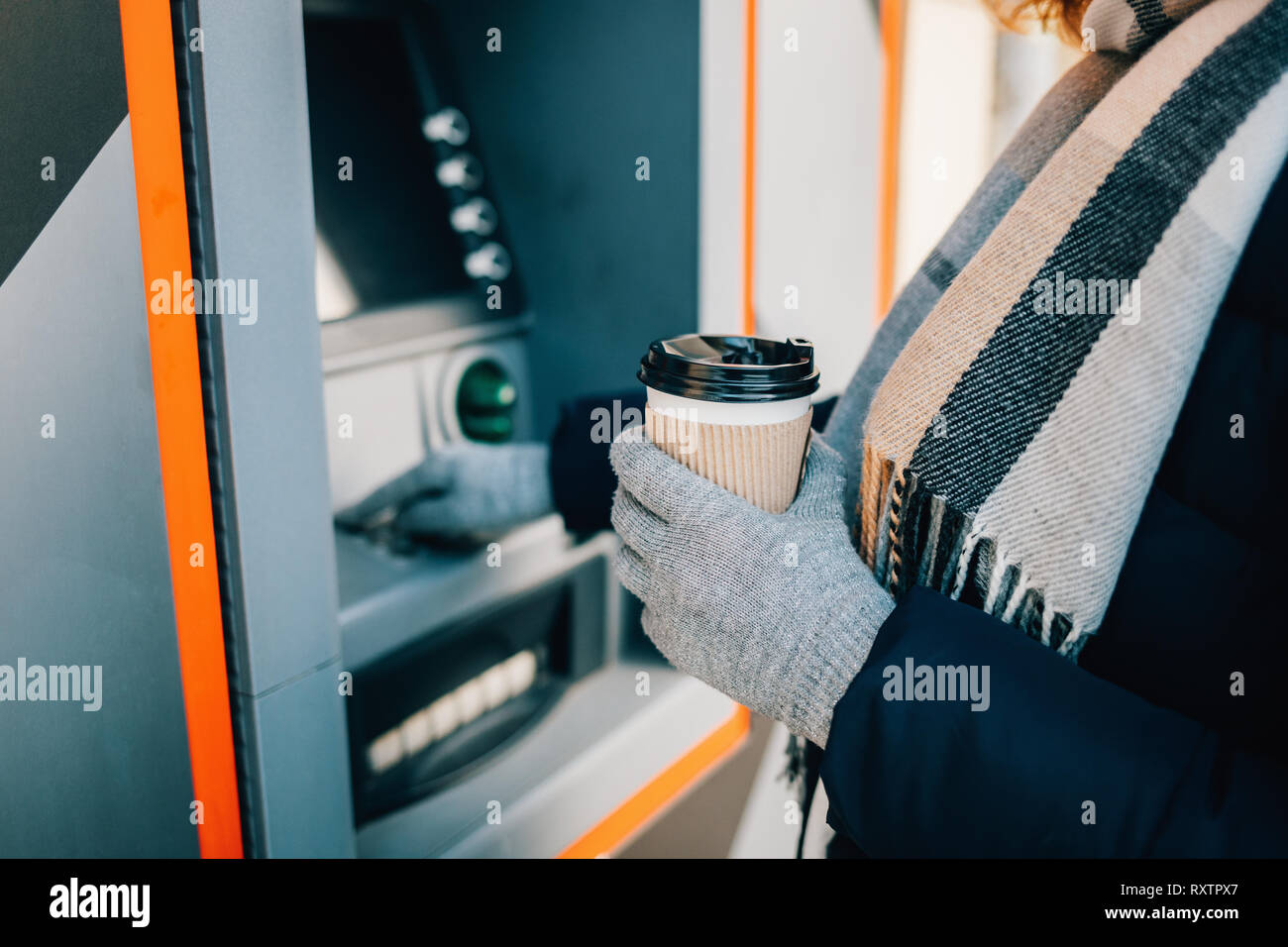 Close-up of young woman in warm clothing holding coffee and using an ATM on city street in winter day. - Stock Image