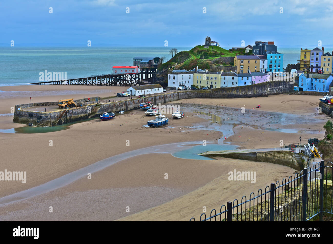 The pretty harbour at Tenby, low tide in Winter. Lifeboat stations old & new  with pastel coloured houses overlooking the sandy North Beach.S.Wales Stock Photo