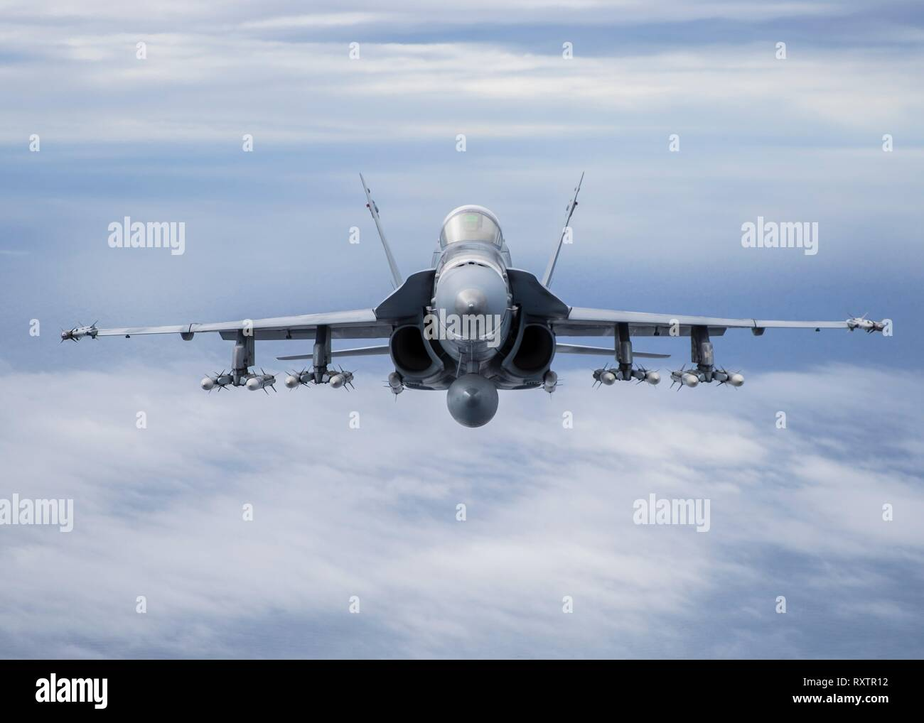 A U.S. Marine Corps F/A-18 Hornet fight aircraft with Marine Fighter Attack Squadron 323, carrying ten AIM-120 and two AIM-9X Air-to-Air missiles, during a training mission over the W-291 training area March 6, 2019 in Southern California. - Stock Image