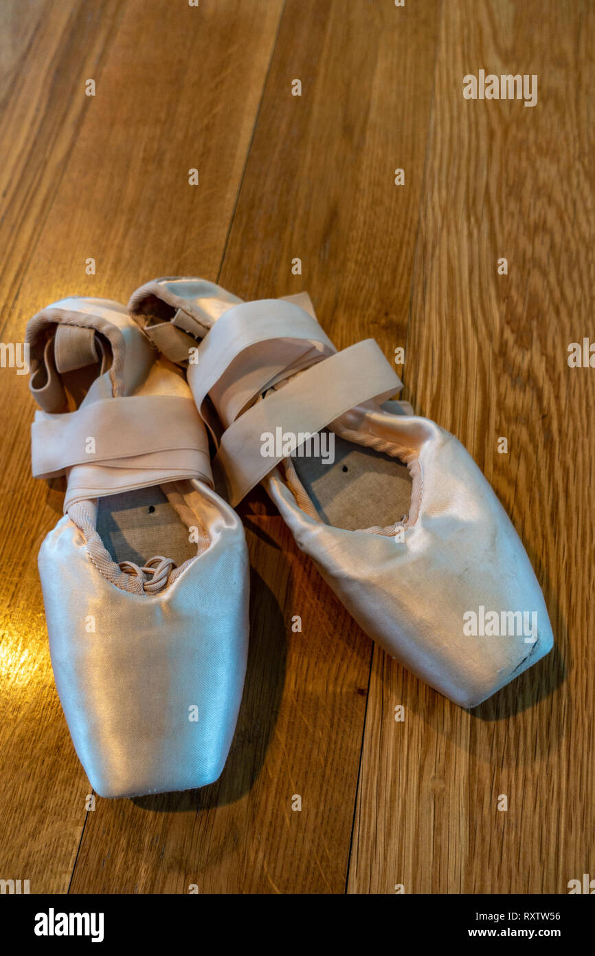 Classical Ballet pointe shoes, Ballerinas Pointe Shoes on a wooden floor - Stock Image