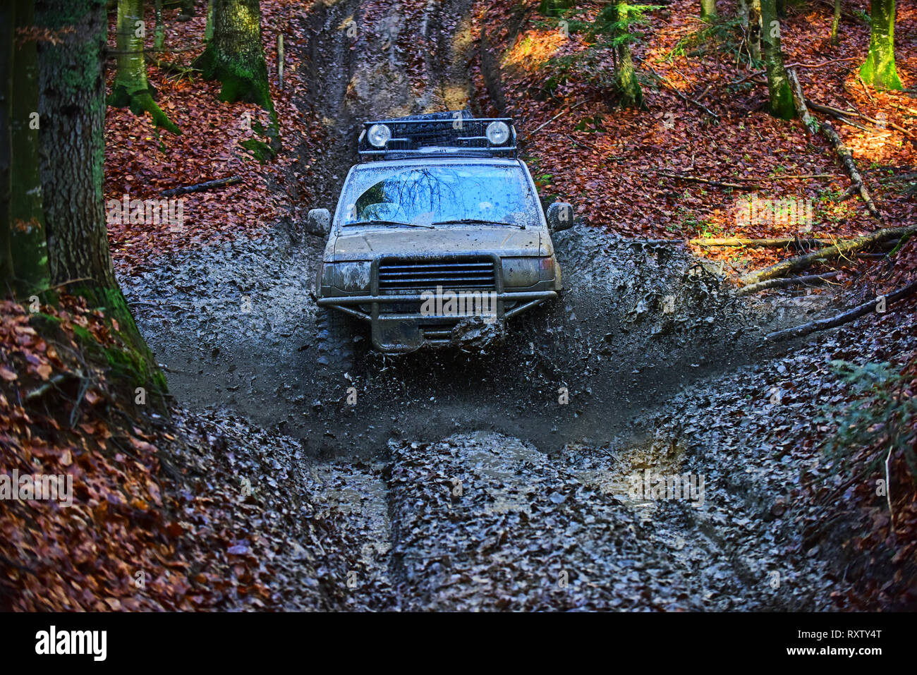 SUV covered with mud stuck in dirt on path - Stock Image