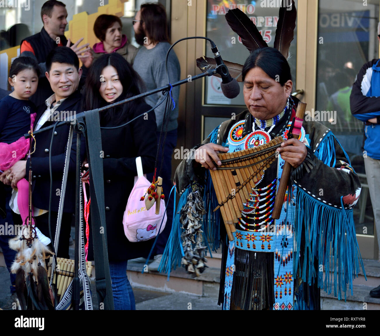 Chinese family watching indigenous pan flute performance during Slavic festival - Stock Image
