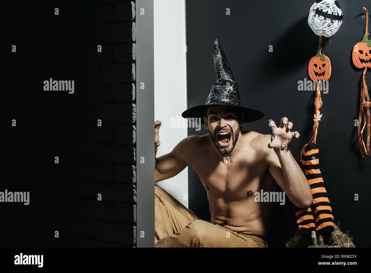 Halloween man in witch hat shouting with grabbing hands - Stock Image
