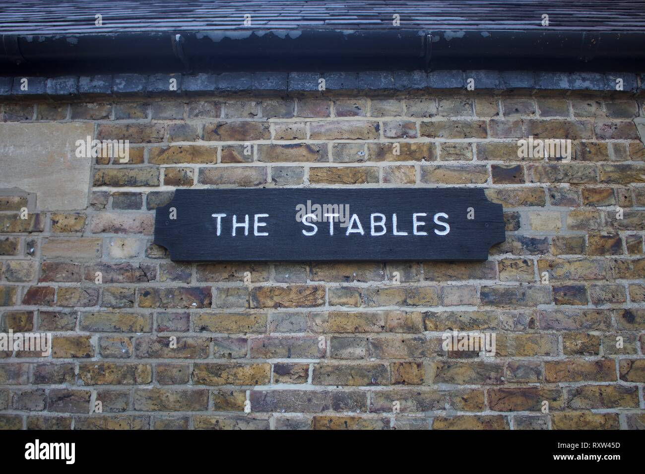 Wooden sign for The Tables with white lettering on black background against a brick wall - Stock Image