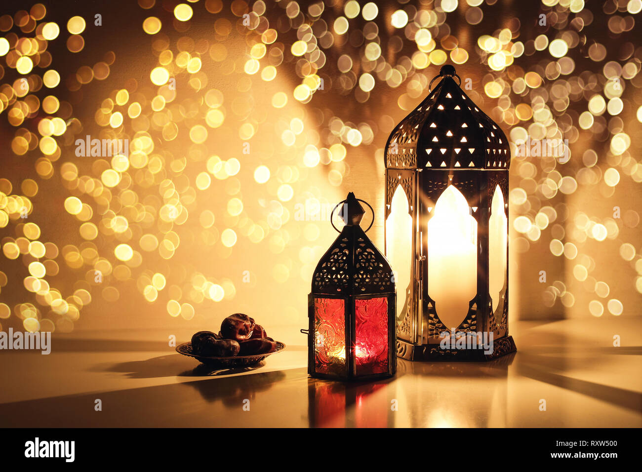 Ornamental Arabic lanterns with burning candles. Glittering golden bokeh lights. Plate with date fruit on the table. Greeting card for Muslim holiday - Stock Image