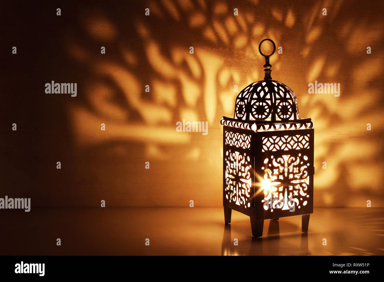 Silhouette of Moroccan ornamental lantern with burning glowing candle. Decorative shadows. Festive greeting card, invitation for Muslim holy month - Stock Image