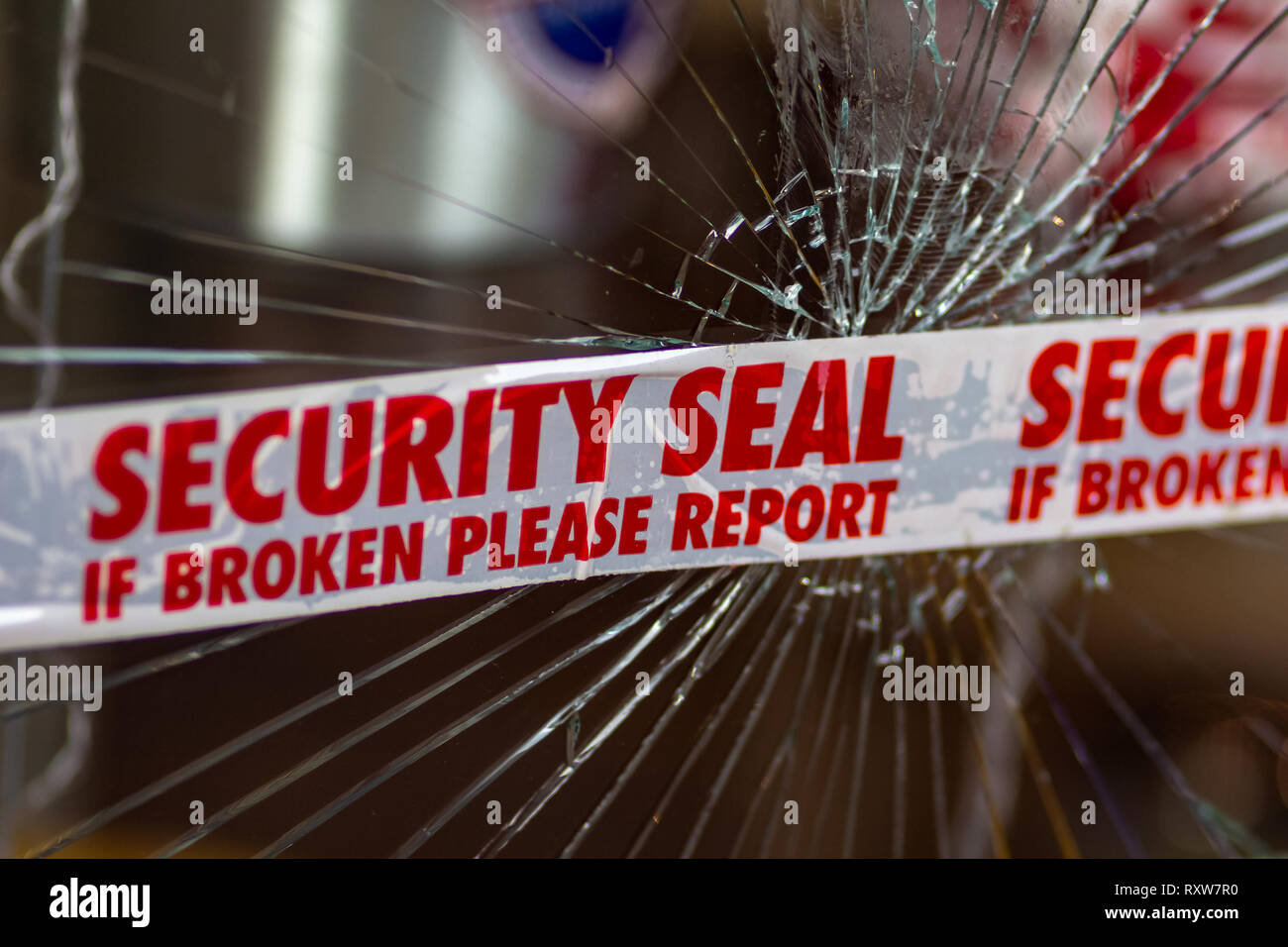 Police Security Seal tape across the broken glass window - Stock Image