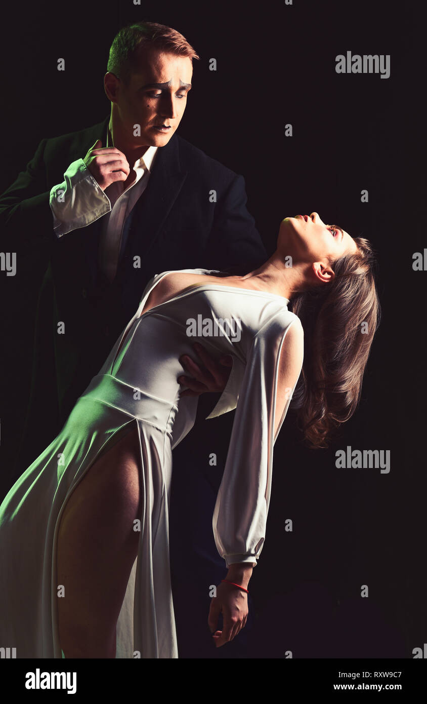 They are all magnificent. Theatre actors miming through body motions. Mime man and woman act in romantic scene. Couple of mime artists perform romance - Stock Image