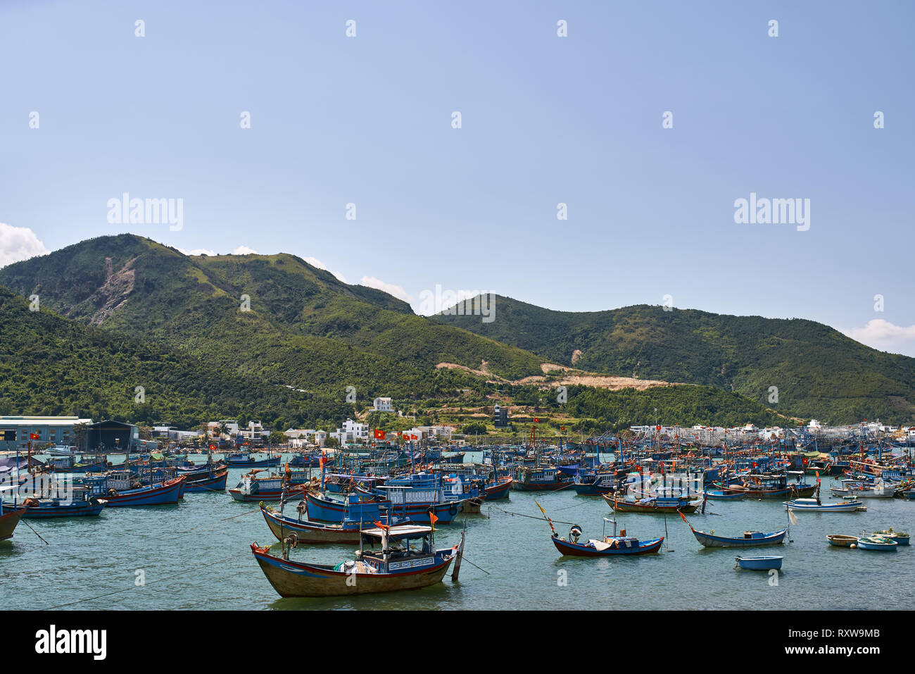 Many colorful wooden fishing boats in the sea bay on the background of the small village and green hills and the blue sky. Sun is shining onto them. H - Stock Image
