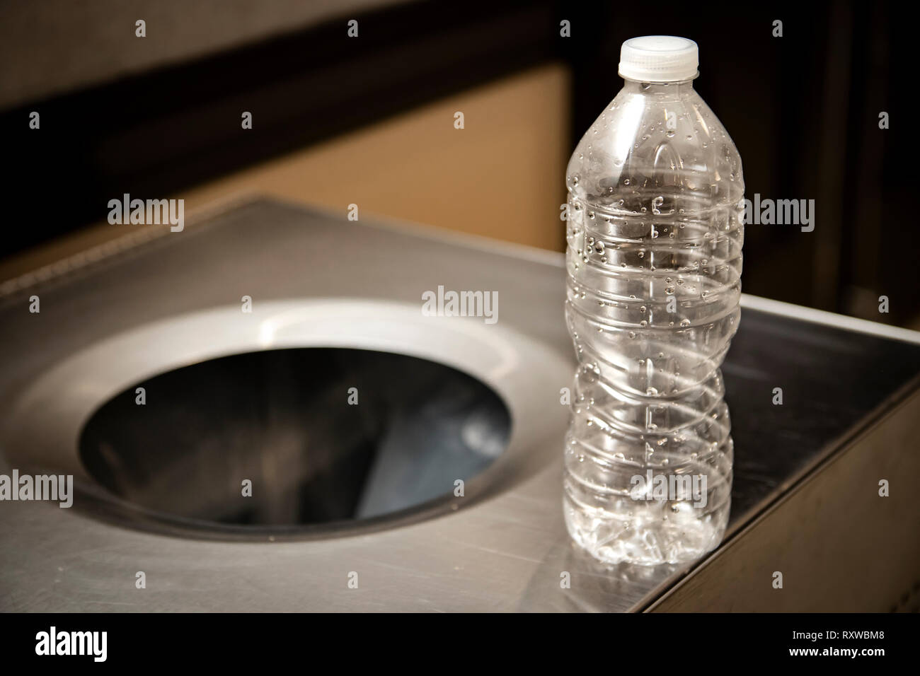 Singe use disposable plastic water bottle next to trash or recycling bin. - Stock Image
