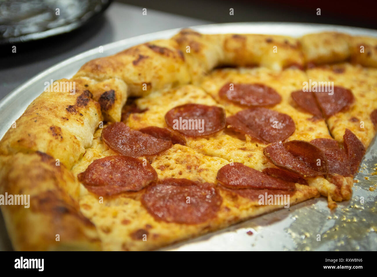 Slices of greasy American pepperoni pizza on a restaurant pizza pie pan. - Stock Image