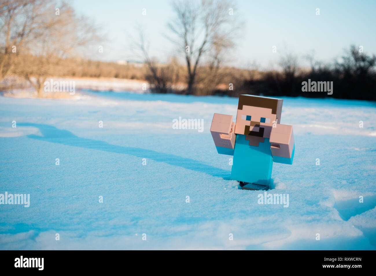 Steve miniature from mine craft posing on the snow. - Stock Image