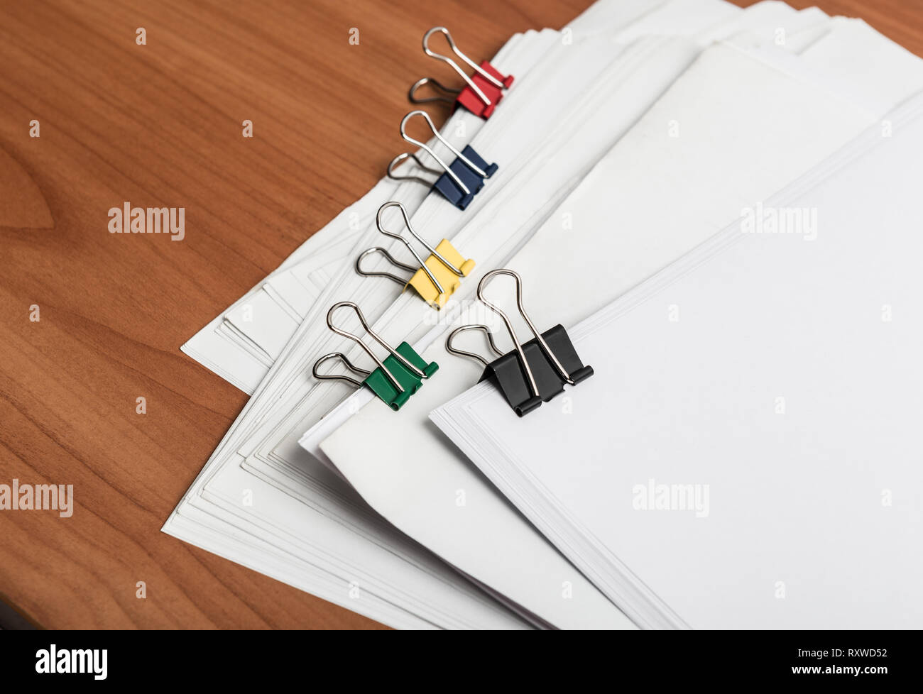 White paper document template with metal color clips on work table side view - Stock Image