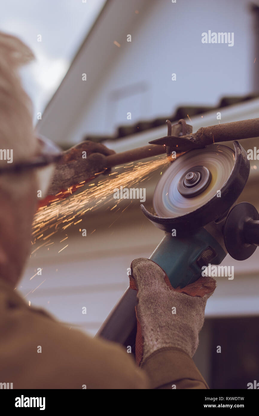 The process of cutting metal with sparks worker cuts the metal with a grinding machine - Stock Image
