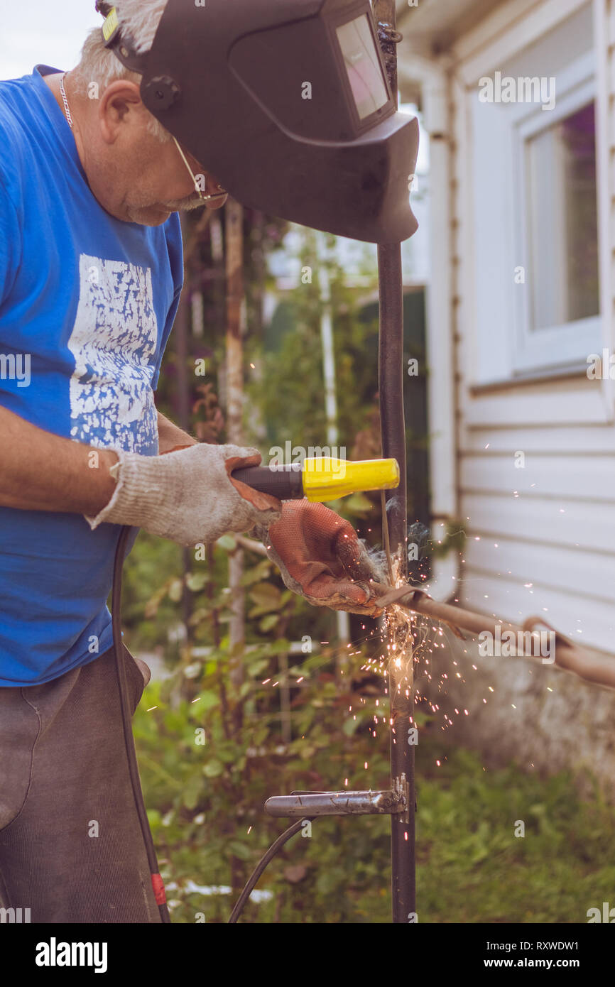 The man working by the welder joins metal structure - Stock Image