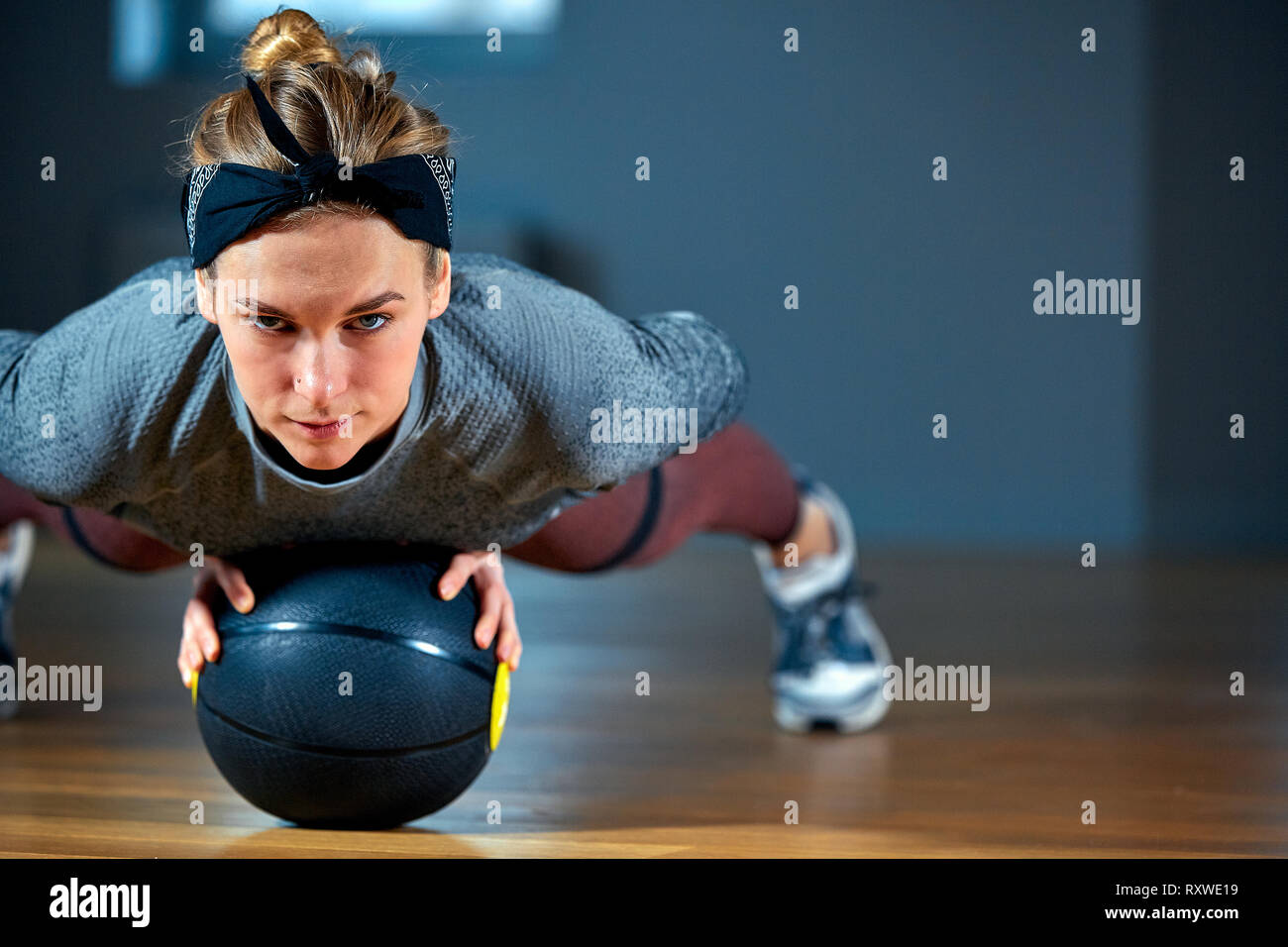 Fit and muscular woman with piercing eyes doing intense core workout with kettlebell in gym. Female exercising at crossfit gym. - Stock Image