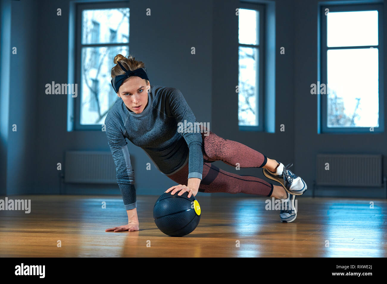Fit and muscular woman doing intense core workout with kettlebell in gym. Female exercising at crossfit gym. Stock Photo