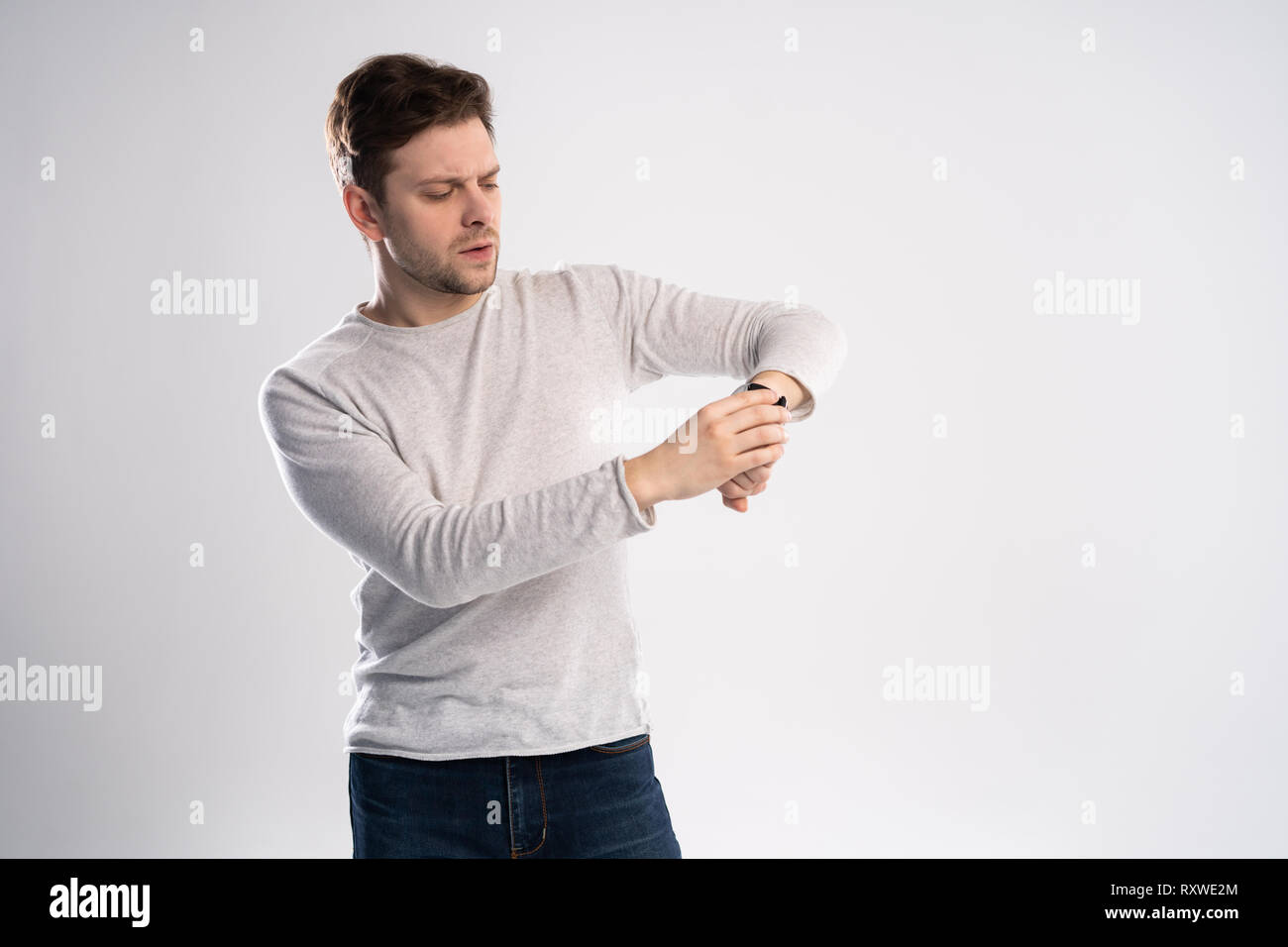 Portrait of a shocked man looking on wrist watch over white background. - Stock Image