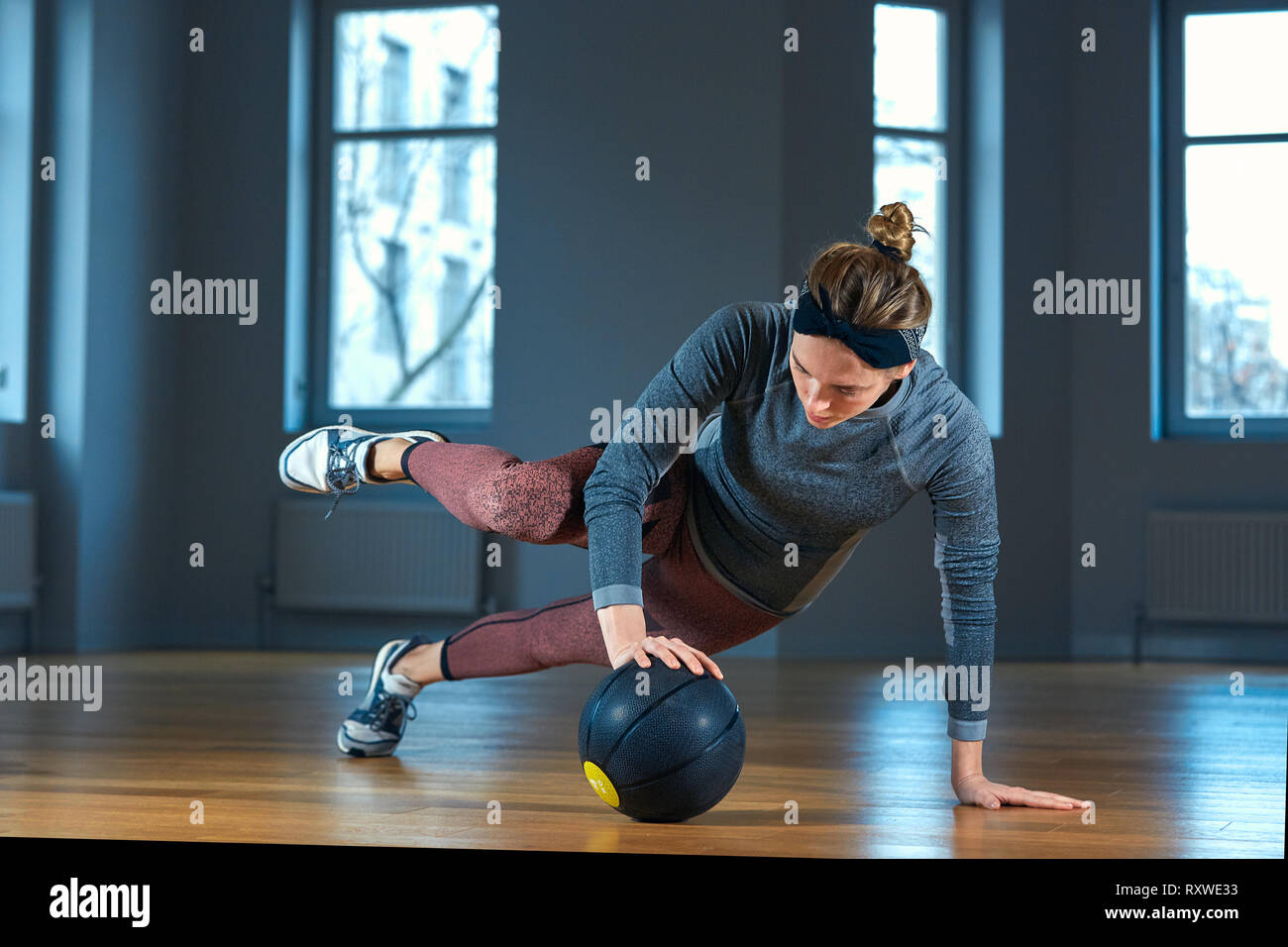 Fit and muscular woman doing intense core workout with kettlebell in gym. Female exercising at crossfit gym. - Stock Image