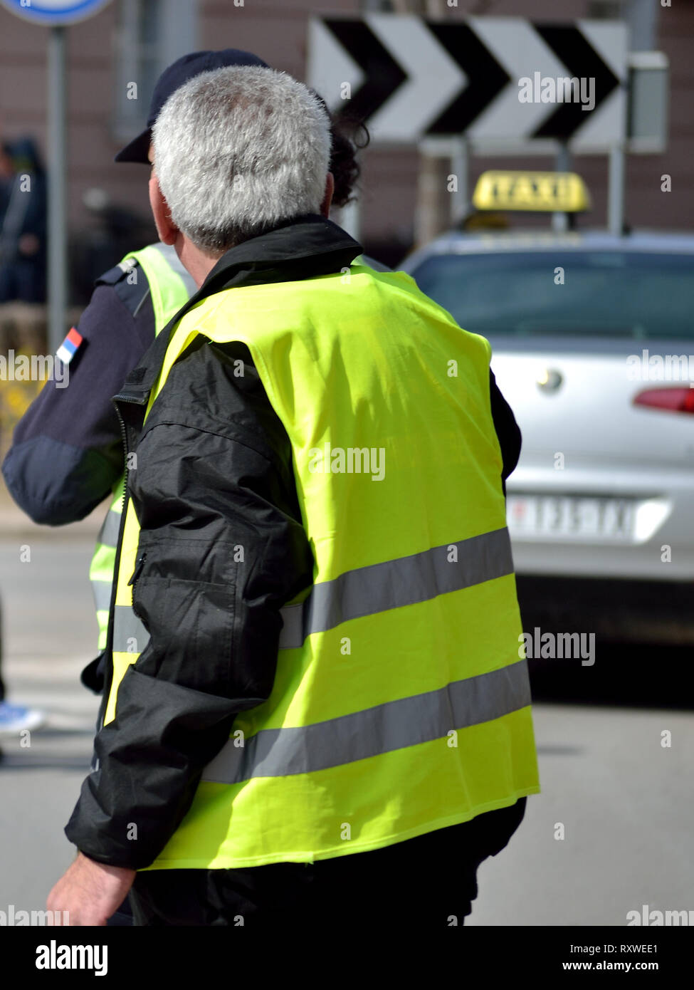 Police officer patrolling a large event in fluorescent yellow waistcoat - Stock Image