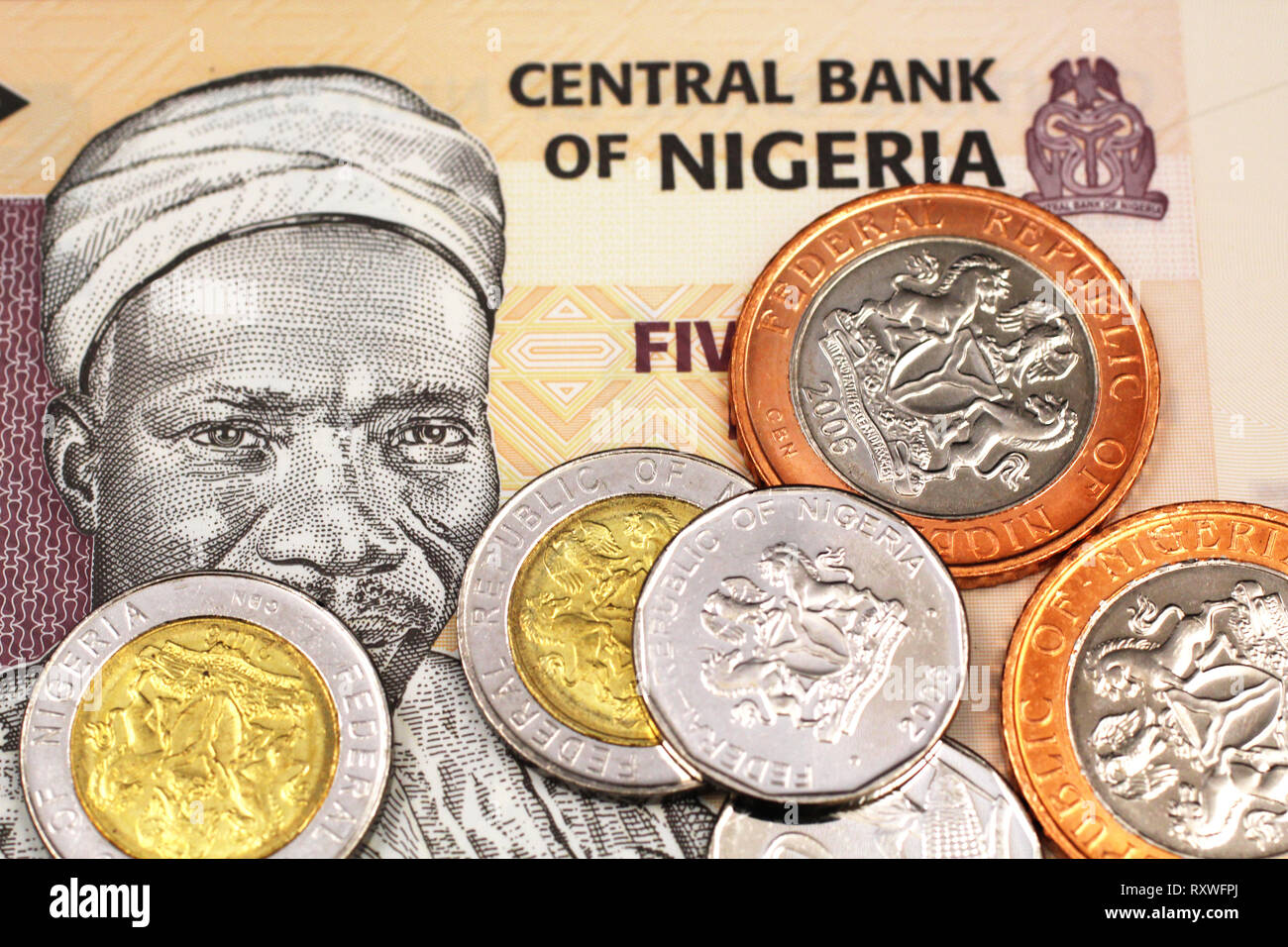 A macro image of miscellaneous Nigerain coins on a five Naira bank note from Nigeria - Stock Image