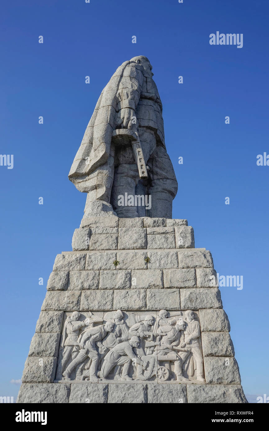 Low vantage view of a monument dedicated to the Russian Red Army with a stone statue of the unknown soldier holding a gun and bas-relief of the advanc Stock Photo