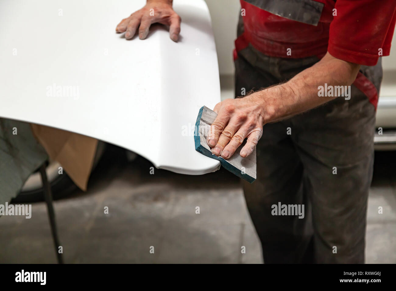 Preparation for painting a car element using emery sponge by a service technician leveling out before applying a primer after damage to a part of the  - Stock Image