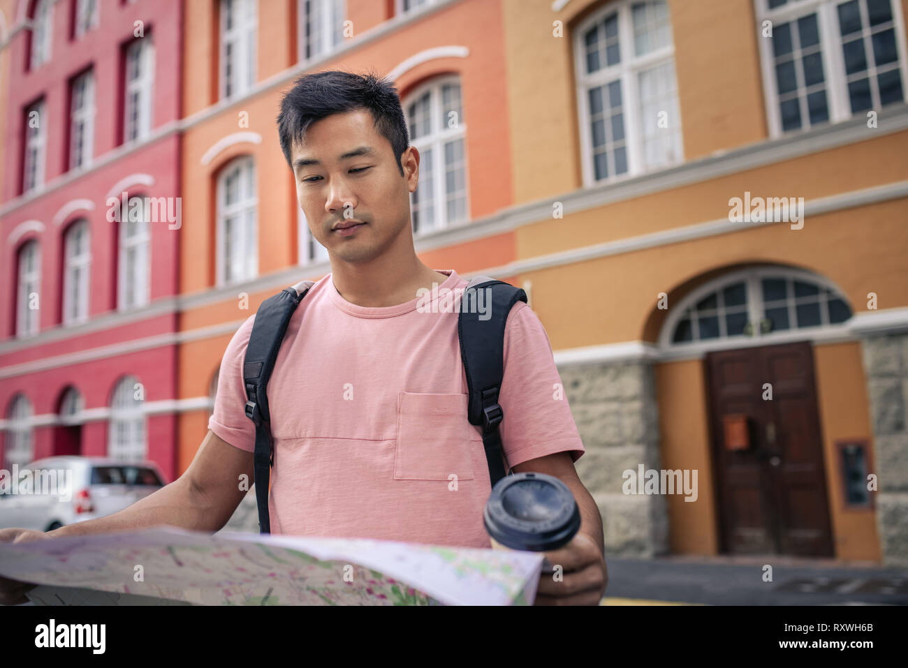 Young Asian man reading a map while exploring the city Stock Photo