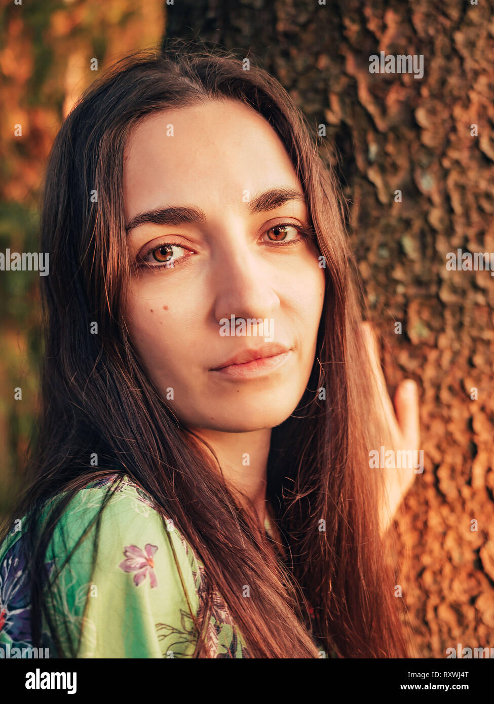 Portrait beautiful caucasian brunette girl with long hair in the forest at sunset leaned against a tree. Unity with nature Stock Photo
