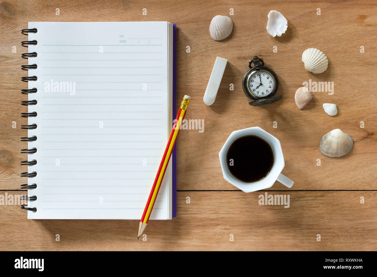 Bank notebook with pencil and eraser laying on the brown table. Vintage clock at 8 o'clock, Black coffee and shells on table. - Stock Image