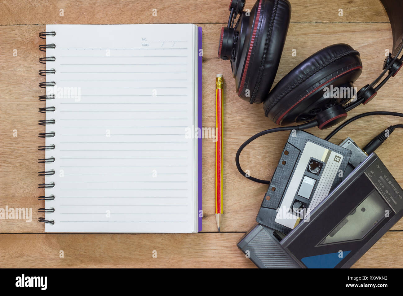 Bank notebook with pencil laying on the brown table. Vintage old tape player with headphones put on the table as well. - Stock Image