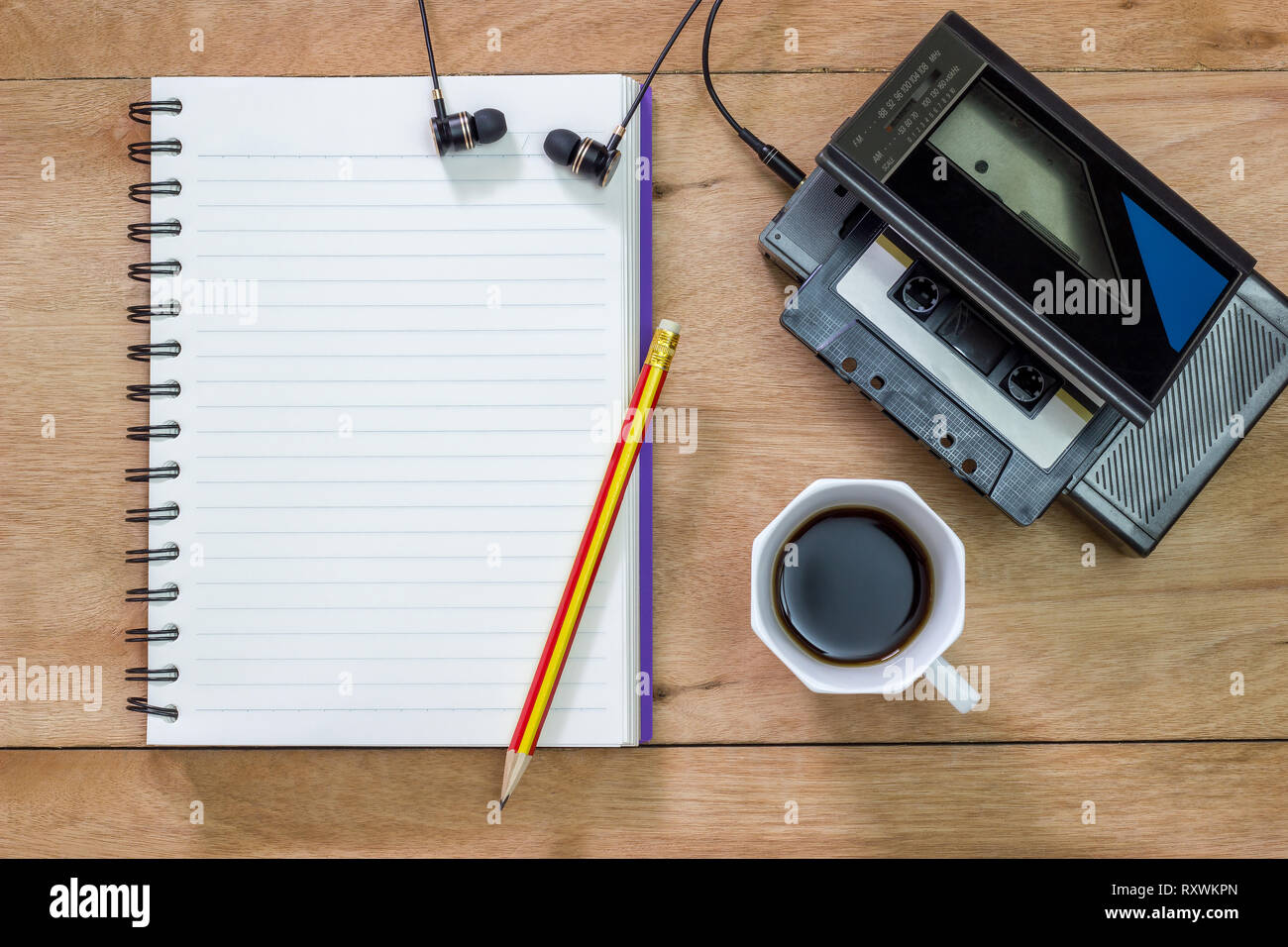 Bank notebook with pencil laying on the brown table. Vintage old tape player with earphones and black coffee put on the table as well. - Stock Image