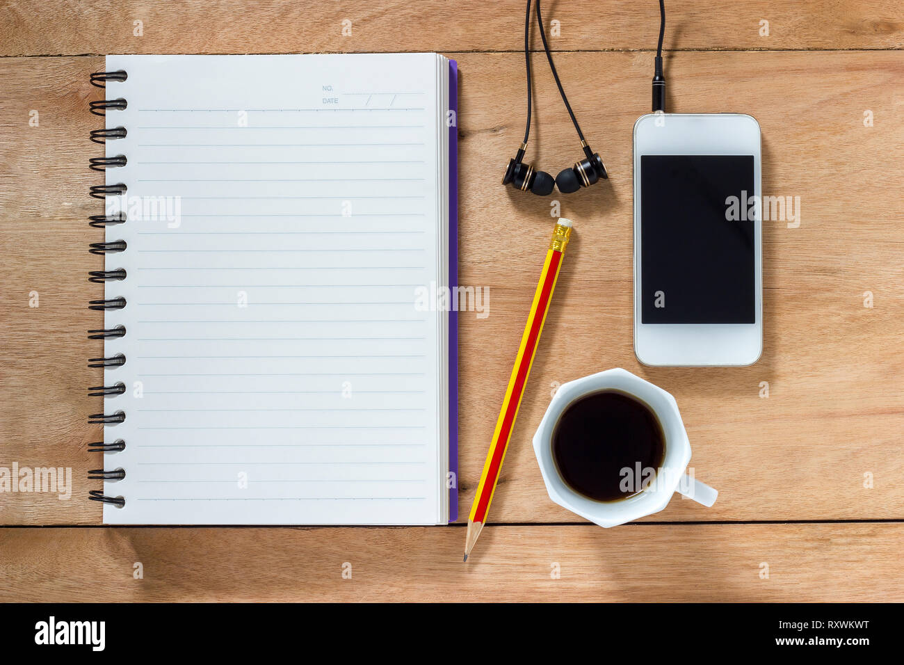 Bank notebook with pencil laying on the brown table. White mobile with earphones and black coffee put on the table as well. - Stock Image