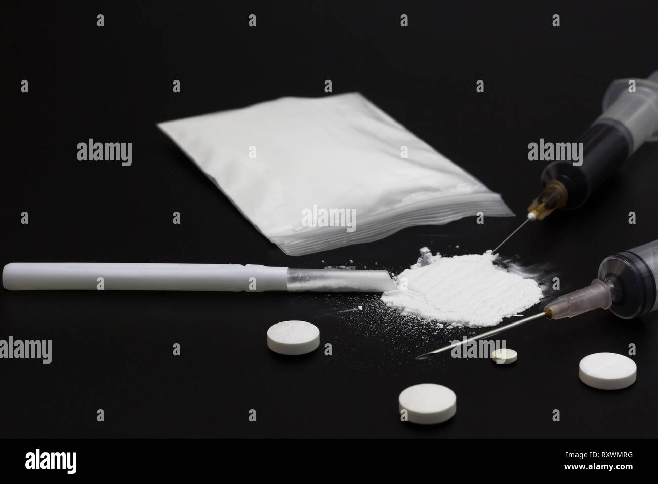 Fake Heroin or diacetylmorphine bag and syringes placed side by side. Low key addictive substance on darkness background. - Stock Image