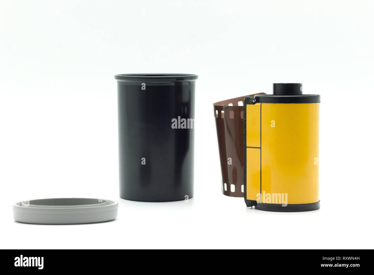 Black film bottle with gray bottle cap and yellow roll film on a white background. Stock Photo