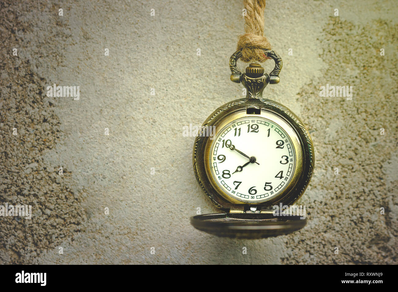 The morning sunlight shines into the ancient old vintage clock, which is tied with hemp rope hanging beside to the cement wall. - Stock Image