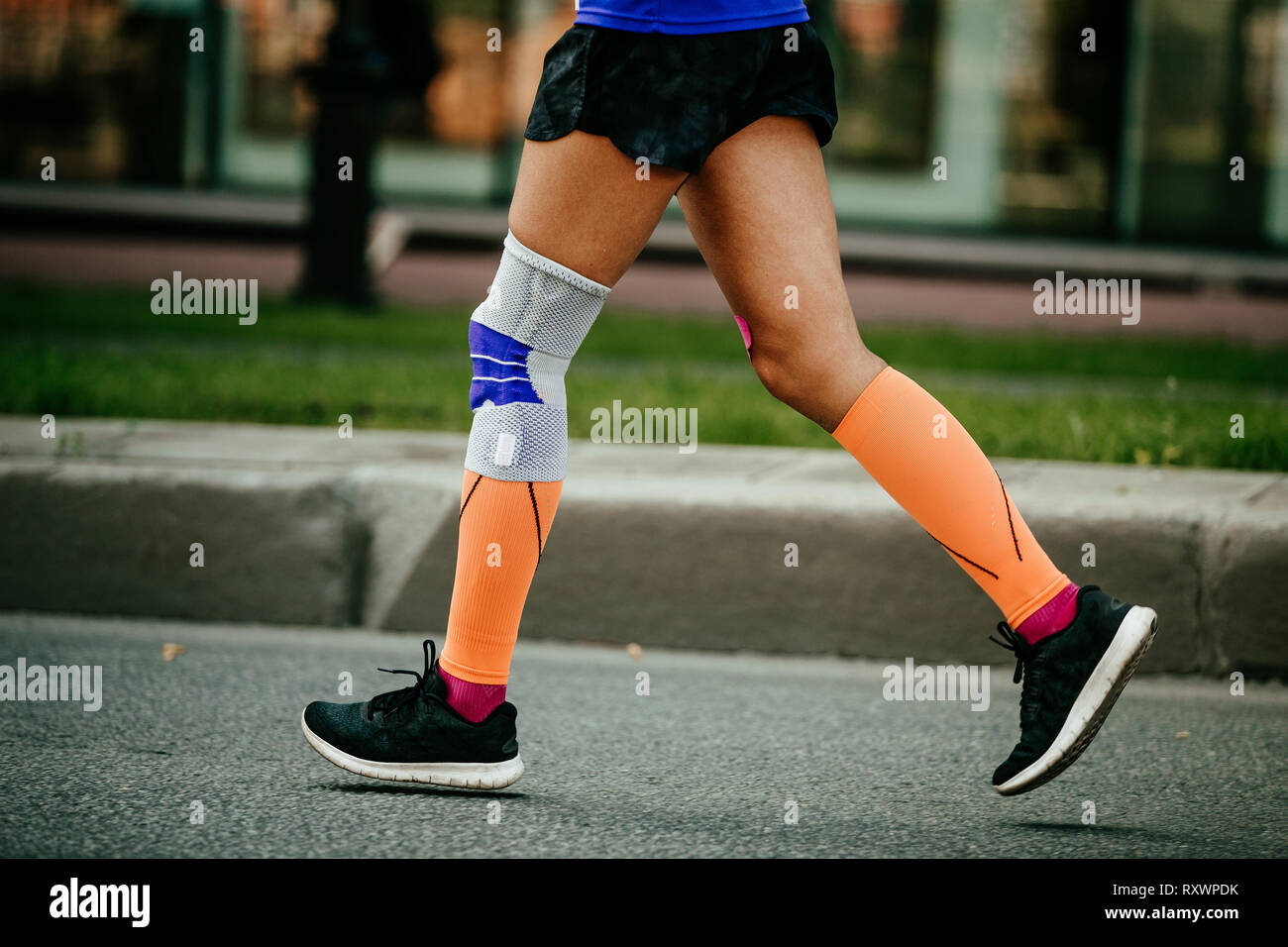 women feet in compression socks and kneepad on knee running - Stock Image