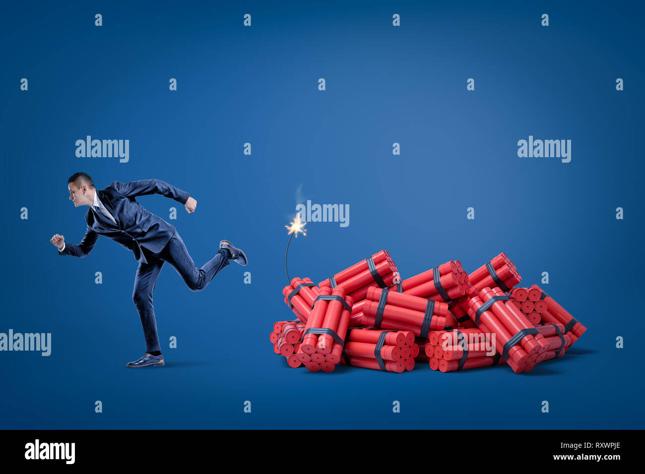 Businessman running away from pack of red tnt dynamite sticks with lighted fuse on blue background - Stock Image
