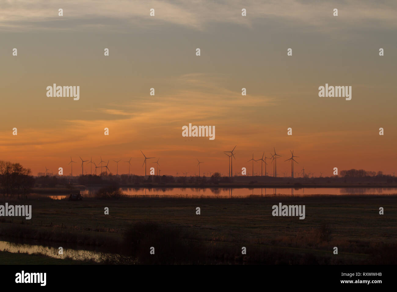 Wind farm in evening light with lake in the foreground. East Frisia, Lower Saxony. Germany. - Stock Image