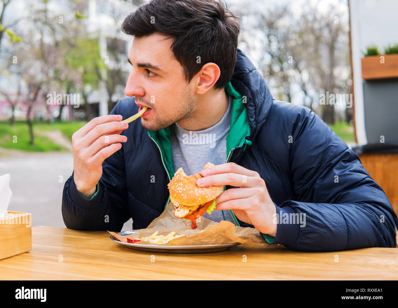 man eating fried potatoes with a burger in street food cafe Stock Photo