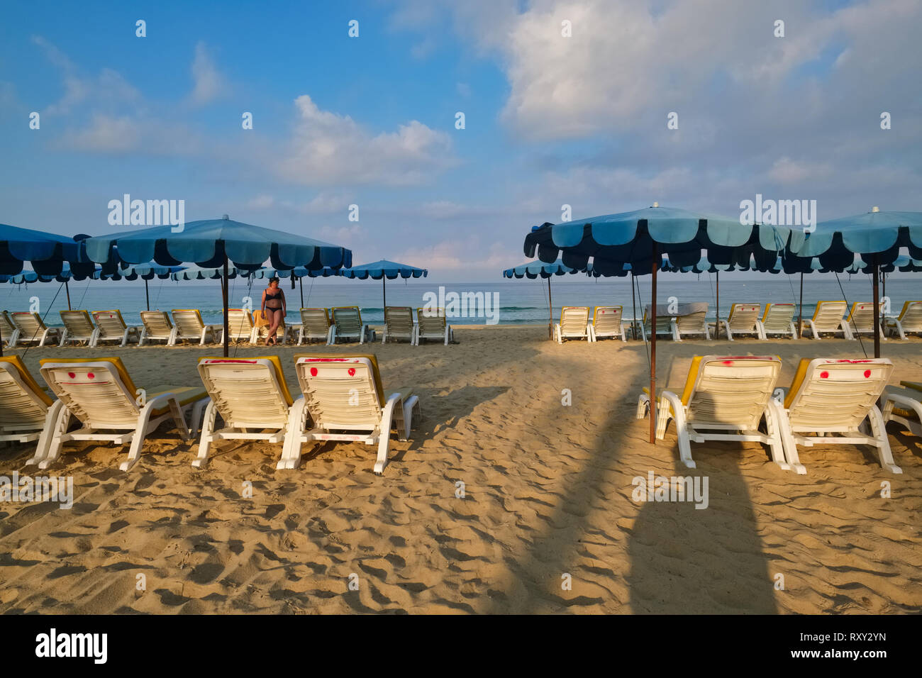 On an early morning, Karon Beach in Phuket, Thailand, with opened parasols and sun chairs lined up, is almost empty, save for a lone woman in the b/g - Stock Image