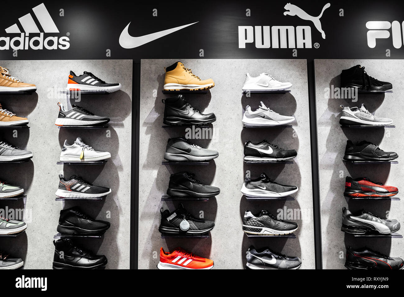 differently f632c f486d Nurmberg, GERMANY - February 27, 2019  The NIKE, ADIDAS, PUMA and FILA  black man sneakers on the shell in the shop. Fashionable foot wear shoes.