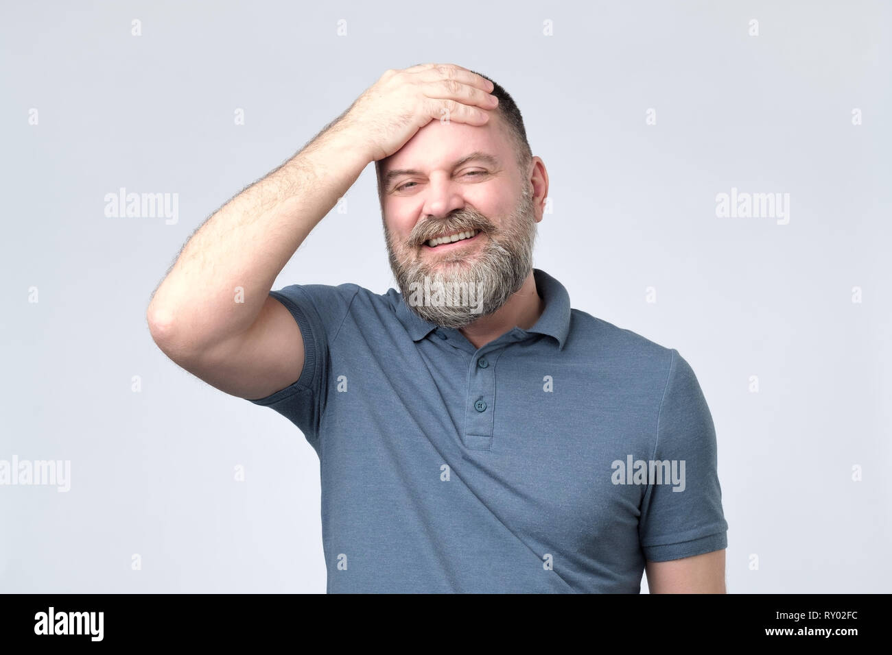 handsome mature man hold his head in hand forgotten something - Stock Image