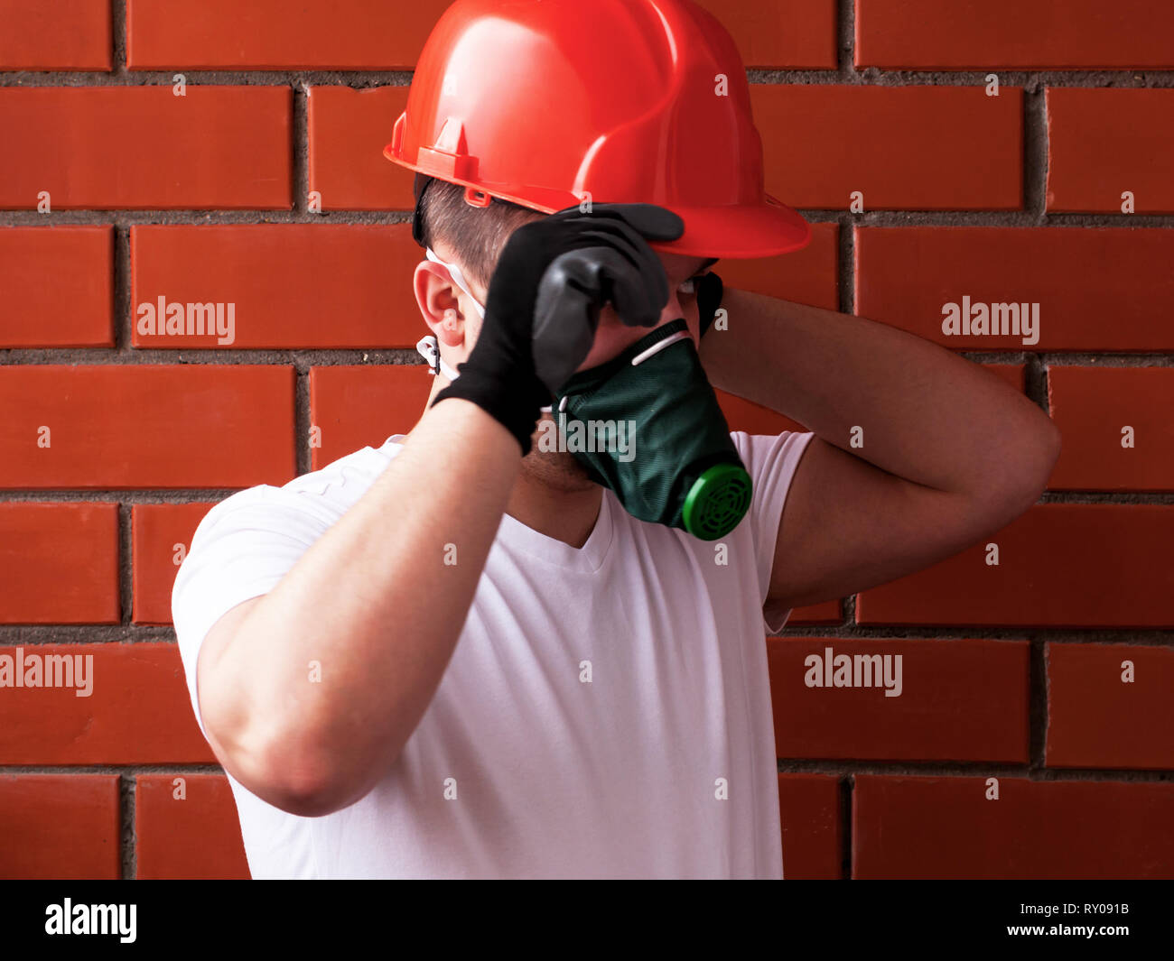 A Man In A Helmet And Respirator Performs Painting Work On A Concrete Ceiling Against A Background Of Brickwork The Concept Is Workplace Safety Diy Stock Photo Alamy